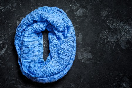 Blue knitted wool circle scarf on a black background with copy space Zdjęcie Seryjne