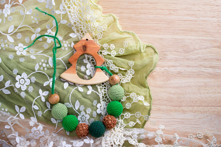 motility: wooden toy Christmas tree and sling necklace made from knitted beads on the table with copy space