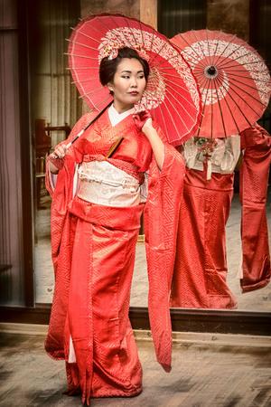 geisha in red kimono with parasol