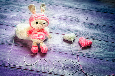 Handmade crochet rabbit toy doll sitting on a skein of wool, two crocheted baloons and love inscription made from the thread, space for text