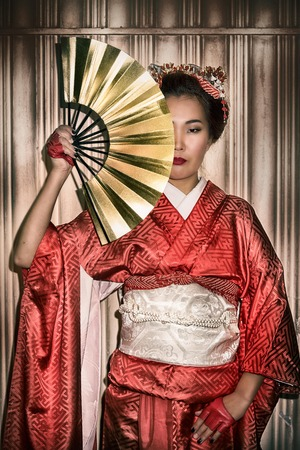 paper fan: Asian woman in traditional red Kimono holding a paper fan, which covers half of her face.