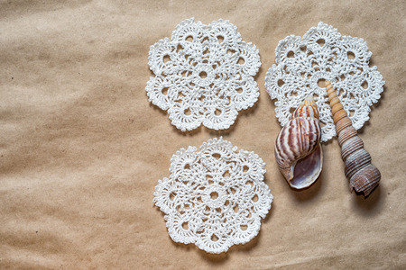 Three Crochet Pattern Coasters On Paper Background And Two