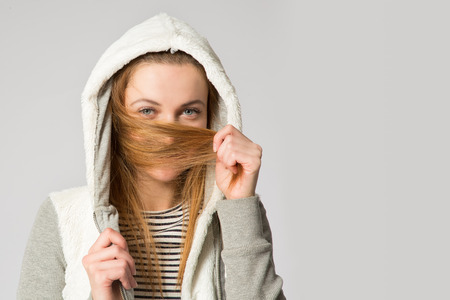 hoody: Portrait of a young woman in a hoody with long messed-up hair in her hands covering her face
