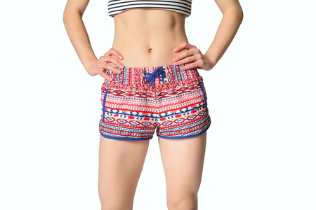 Close up of woman in shorts with hands on waist, front view. Young beautiful woman isolated on the white background. Girl model. Studio shot.