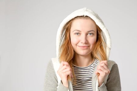 hoody: young cheerful casual caucasian woman wearing white hoody over gray background, studio shot. copy space at the side. Stock Photo