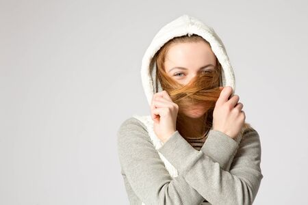 vest in isolated: Portrait of a laughing girl, hiding her face by hair. Pretty young woman with long hair covered her face with a cross hair over grey background, studio shot.