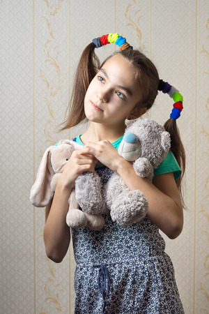 11 year old: 11 year old girl with two soft toys dreamily nostalgic looking up. Stock Photo