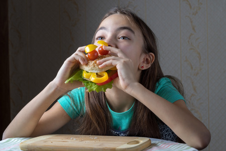11 year old: 11 year old girl with pleasure eats a hamburger