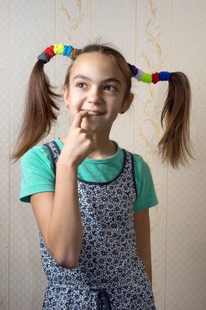 11 year old: 11 year old girl with pigtails like Pippi Longstocking with a mischievous look on her face and her finger to her mouth thoughtfully looking up. Stock Photo