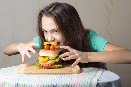 11 year old: 11 year old girl jumps on a burger, the concept of hunger and unhealthy eating habits.