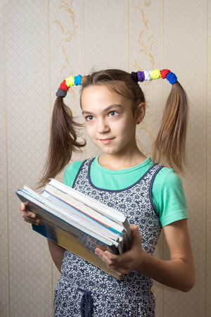 11 year old: 11 year old girl with funny tails is with a pile of books. concept of school education Stock Photo