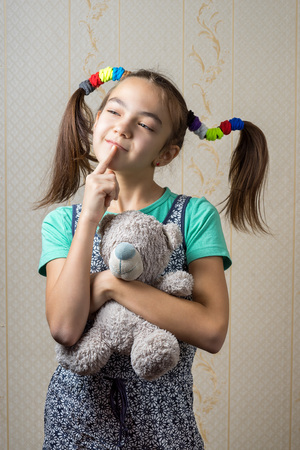 11 year old: 11 year old girl with a teddy bear thoughtfully looking up with her finger to the mouth.