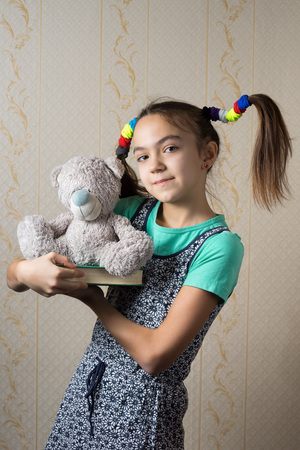 11 year old: happy 11 year old girl with funny tails is holding a book and teddy bear