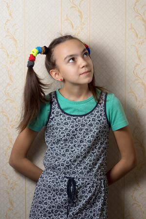 11 year old: 11 year old girl is leaning against the wall and looks up dreamily