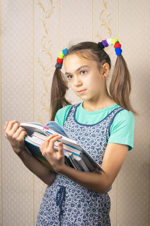 11 year old: 11 year old girl thoughtfully standing with a stack of books Stock Photo