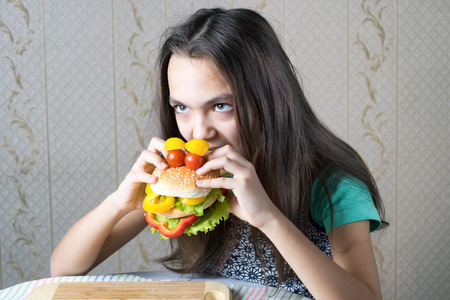 11 year old: 11 year old girl bites her teeth into a burger, made in the form of faces with eyes of cherry tomatoes.