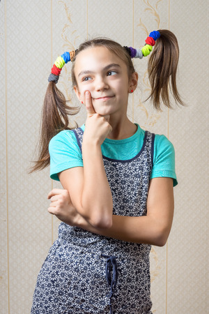 11 year old: 11 year old girl with pigtails like Pippi Longstocking is thoughtfully, pressing a finger to her cheek. the concept of decision making. Stock Photo