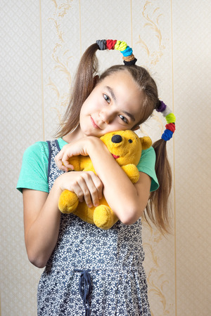 11 year old: happy 11 year old girl hugging a yellow teddy bear toy