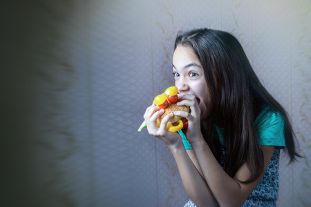 11 year old: 11 year old girl bites her teeth into a burger, made in the form of faces with eyes of cherry tomatoes. Copy space for your inscription. Stock Photo