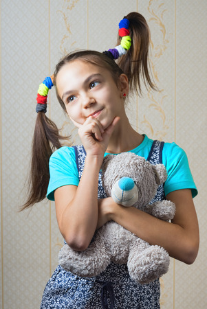 11 year old: 11 year old girl with funny tails hugging a teddy bear Stock Photo