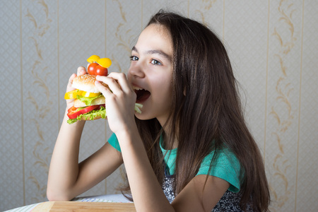 11 year old: 11 year old girl eating a hamburger, side view