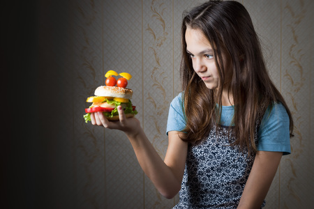 11 year old: 11 year old girl holding at arm hamburger decorated as smiley face with eyes of cherry tomatoes, and looks at it.