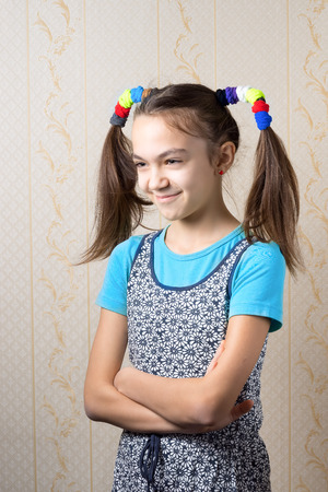 11 year old: portrait of a smiling 11 year old girl with funny tails in the style of Pippi Longstocking standing with arms crossed. Stock Photo