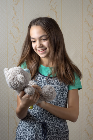 11 year old: happy 11 year old girl holding a teddy bear and looking at him with love