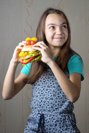 11 year old: 11 year old girl with a hamburger in hand looking up with the question of whether to eat junk food. Stock Photo