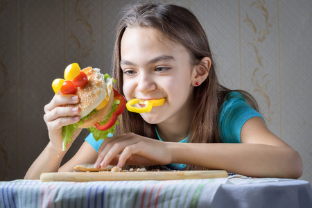 11 year old: 11 year old girl with pleasure eats a hamburger - a piece of bell pepper sticks out of her mouth, crumbs on the table.