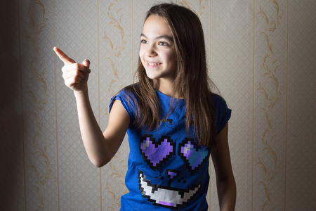 11 year old: smiling 11 year old girl pointing her finger sideways Stock Photo