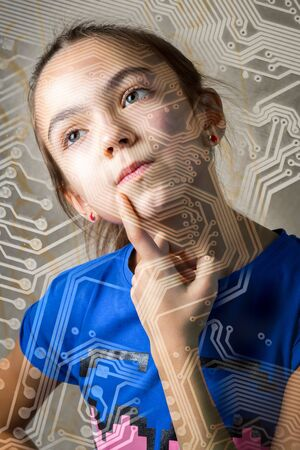 11 year old: 11 year old girl looks thoughtfully through the silhouette of a computer motherboard, leaning a finger to her cheek. the concept of a new technological generation of college information technology.