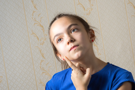 11 year old girl thoughtfully looking up, leaning a finger to her cheek Stock Photo