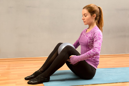 activ: woman sitting with a ball between the knees on the mat. a break in sports training. Stock Photo