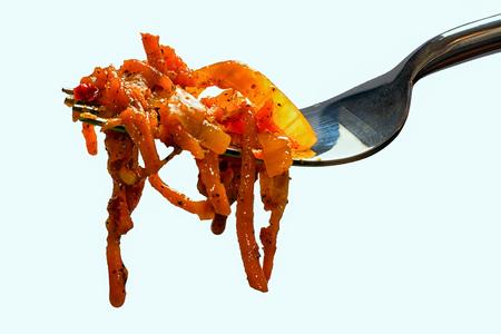 korean salad: Korean carrot salad on forks. Isolated on white