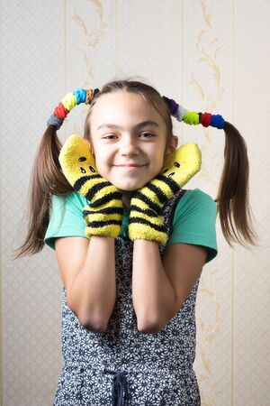 11 year old: 11 year old girl with funny tails of mischievous gum hair, dressed in a shirt and dress, in mittens, the hands are near the face in form of ears.