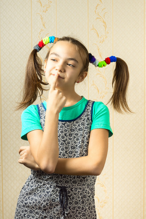 11 year old: Portrait of a 11 year old girl with funny tails in her hair, put his finger to his lips and think with a mischievous expression Stock Photo