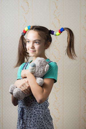 11 year old girl hugging a teddy bear Stock Photo