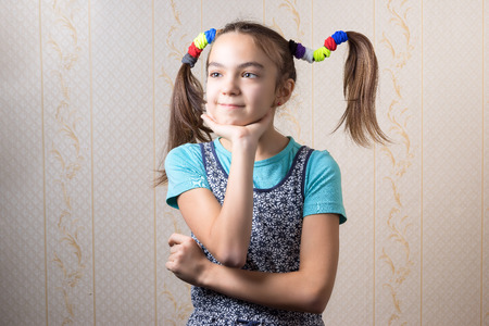 11 year old: 11 year old girl with funny tails thoughtfully propped her chin to the hand
