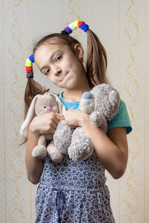 scrunchy: portrait of a pensive child biting her lip with soft toys, teddy bear and rabbit
