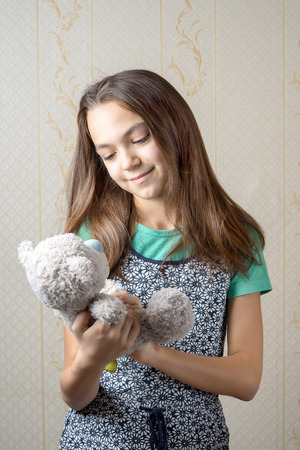 11 year old: 11 year old girl holding a teddy bear and looking at him with love