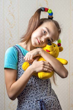 11 year old: 11 year old girl gently huggs her toy pooh bear