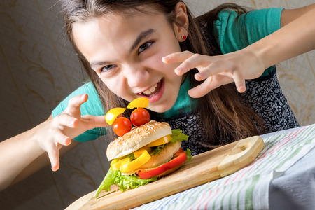 11 year old: 11 year old caucasian girl runs at on a burger to eat it. Hamburger in the form faces of tomatoes as eyes and bread with lettuce leaf in the form of a mouth. Diagonal composition, close up portrait.