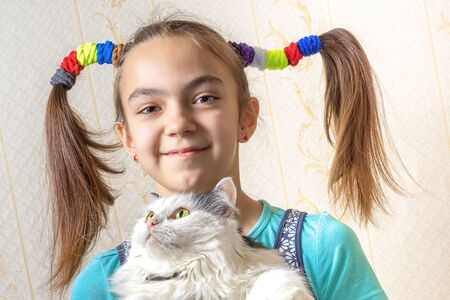 11 year old: Portrait of a 11 year old girl with two funny ponytails of hair elastics holding the cat in her arms, close view