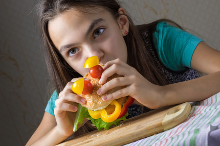 11 year old: Portrait of a 11 year old girl who eats chisburger in the form of faces Stock Photo
