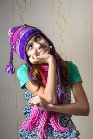 11 year old: Portrait of a 11 year old girl in a shirt and a knitted hat and scarf, looking up pensively.
