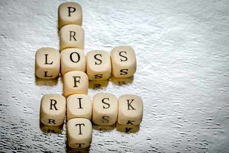 perdidas y ganancias: profit loss risk crossword on a wooden cubes on a shiny silver background
