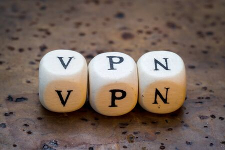 VPN text on wooden cubes on a brown cork background