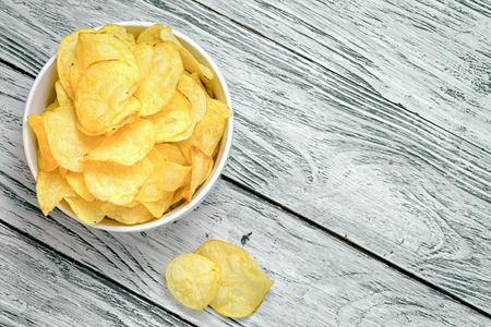 Potato chips in bowl on a wooden background, top view. Salty crisps scattered on a table. Stockfoto