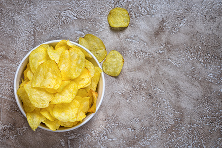 Potato chips in bowl on a grungy neutral cement background, top view. Salty crisps scattered on a table. Stockfoto
